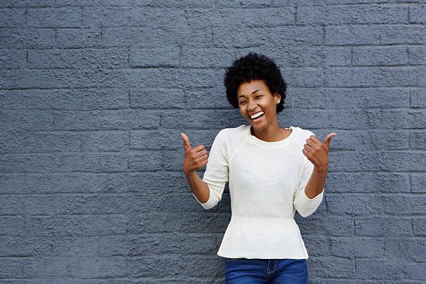 lächelnde junge afrikanische frau mit daumen hoch-schild - dynamische posen stock-fotos und bilder