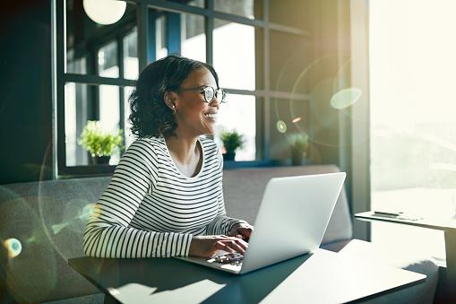 웃는 젊은 아프리카 여자 그녀의 노트북으로 온라인 작업 공부에 대한 스톡 사진 및 기타 이미지