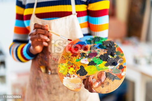 istock Smiling young afro woman holding color palette and paintbrush 1139826864