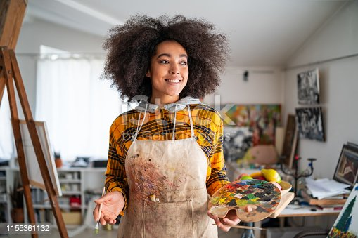 469937444 istock photo Smiling young afro woman holding color palette and paintbrush 1155361132