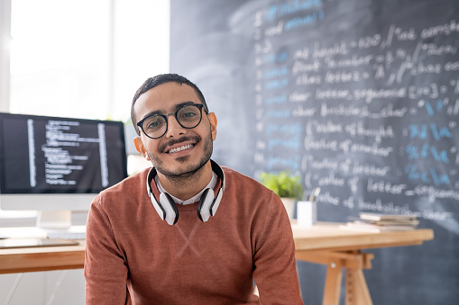 Portrait of smiling young Arabian programmer in eyeglasses sitting in modern office of IT company