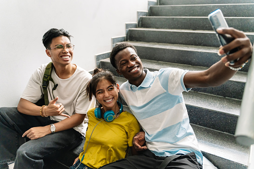 Smiling young Asian and African teenager student friends taking photo selfie with phone in the stairs of Secondary School