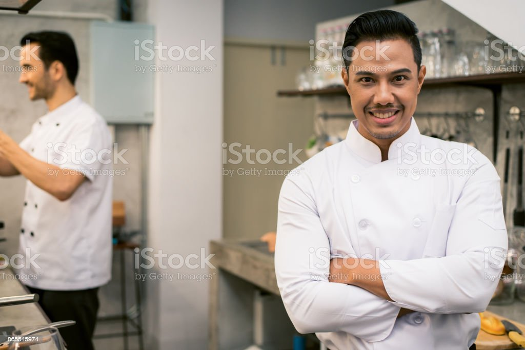 Smiling young asian chef in the kitchen interior of the restaurant. Vintage filtered image. stock photo