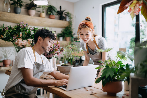 Smiling young Asian couple, the owners of small business flower shop, discussing over laptop on counter against flowers and plants. Start-up business, business partnership and teamwork. Working together for successful business