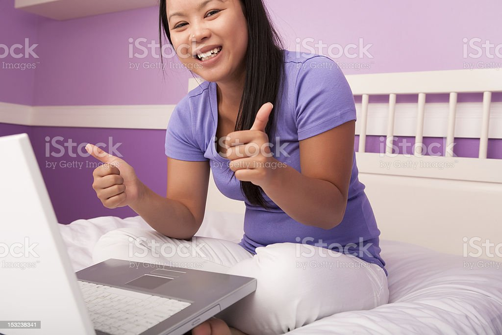 Smiling young asian female using laptop on bed royalty-free stock photo