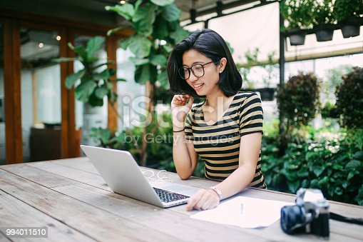 Portrait of a young Asian freelancer woman, working or just relaxing and browsing the web in the co-working space or her apartment. Freelancer - digital nomad concepts in Asia, Thailand.