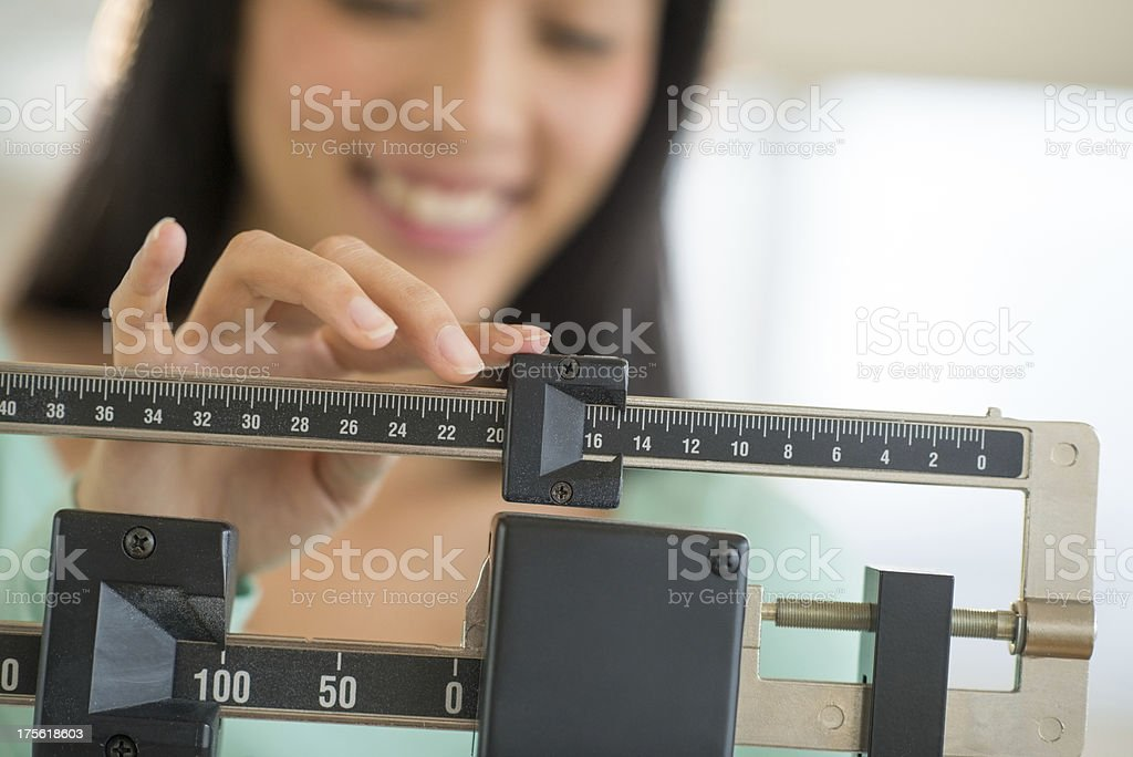 Smiling young Asian woman adjusting a weight scale stock photo
