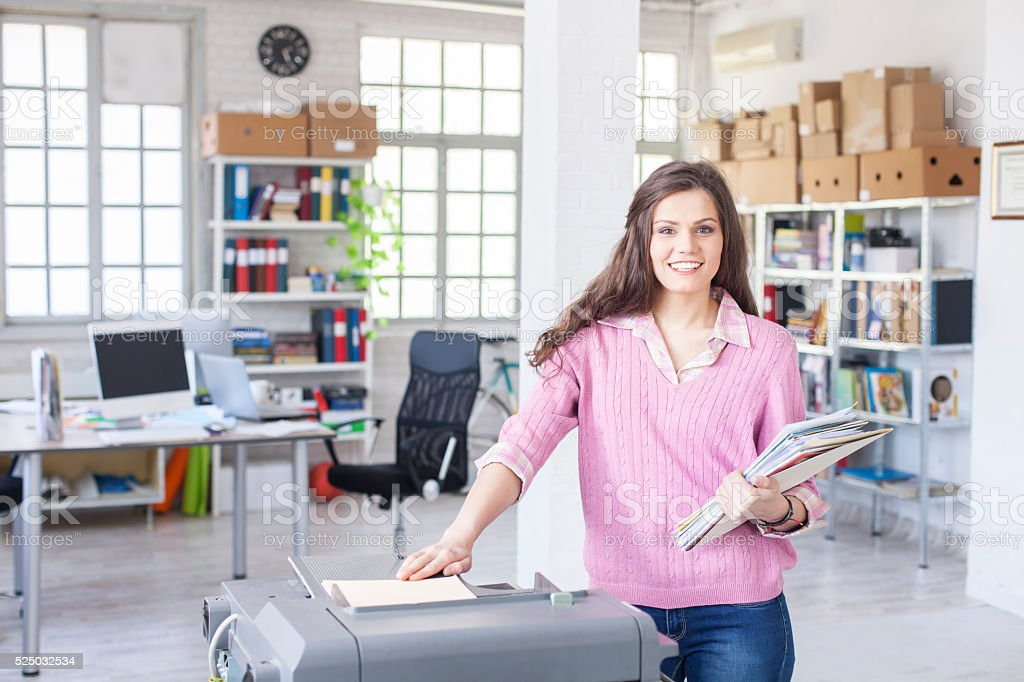 Smiling young assistant using copy machine at work stock photo