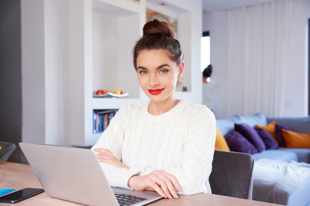 Cтоковое фото Smiling young attractive woman with laptop sitting at home and studying
