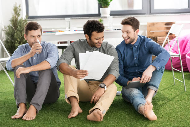 Smiling young barefoot businessmen sitting with papers and using digital tablet, business teamwork concept stock photo