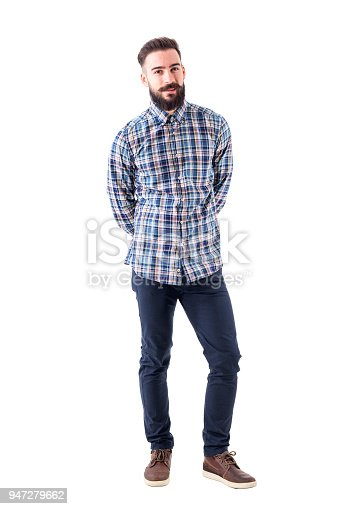 931173966istockphoto Smiling young bearded man biting lips and looking at camera with hands behind back 947279662