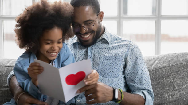 Smiling young biracial dad and daughter read postcard together Happy young biracial father and small ethnic daughter sit on couch at home reading handmade postcard together, loving little african American girl present card greeting with birthday smiling dad birthday wishes for daughter stock pictures, royalty-free photos & images