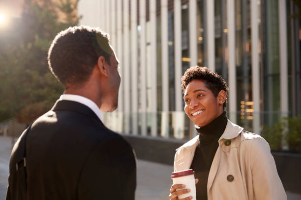 Smiling young black businesswoman standing on the street with a takeaway coffee, talking to her male colleague, selective focus Smiling young black businesswoman standing on the street with a takeaway coffee, talking to her male colleague, selective focus face to face stock pictures, royalty-free photos & images