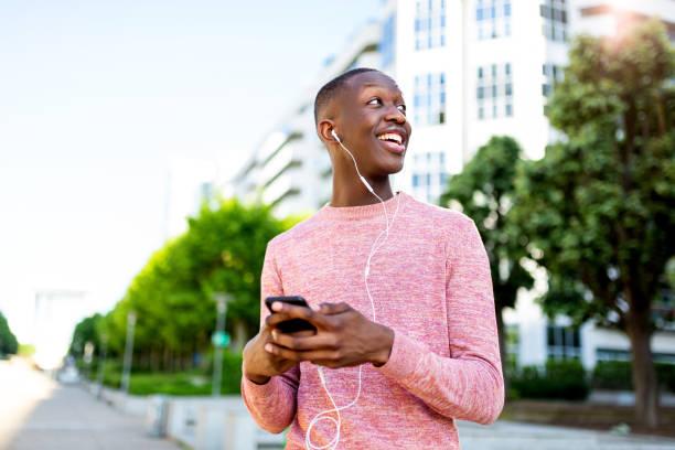 lächelnder schwarzer Mann, der Musik mit Telefon und Kopfhörern hört – Foto