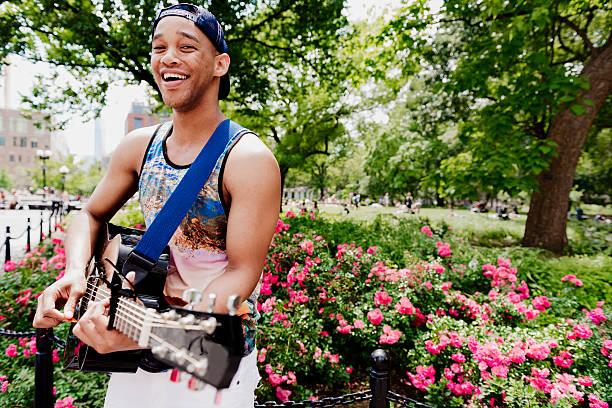 Sonriente joven negro hombre tocando guitarra acústica parque de la ciudad de Nueva York - foto de stock