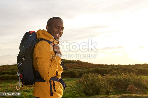 Side portrait of smiling young black man with backpack standing outdoors during sunrise