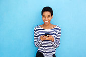 istock smiling young black woman holding cellphone by blue background 868866054