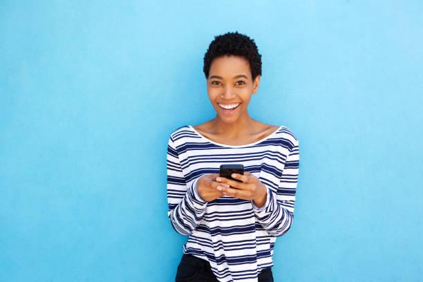 souriante jeune femme noire tenant le téléphone portable de fond bleu - belle femme africaine photos et images de collection