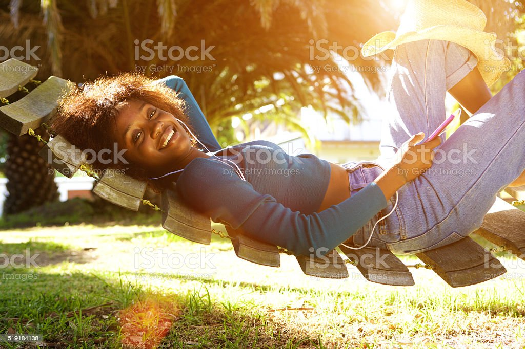 Smiling young black woman listening to music with smart phone stock photo