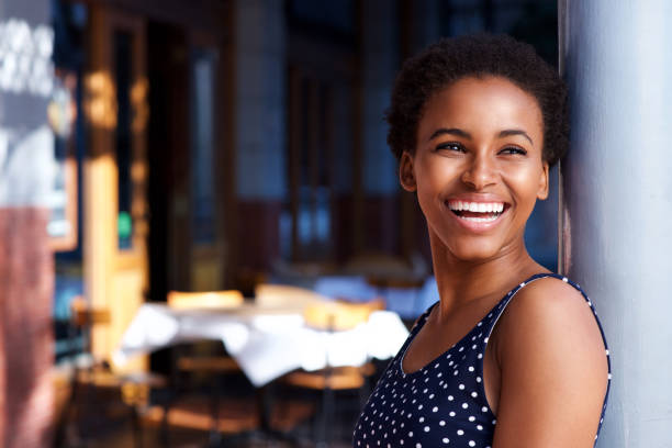 smiling young black woman standing outside - belle femme africaine photos et images de collection