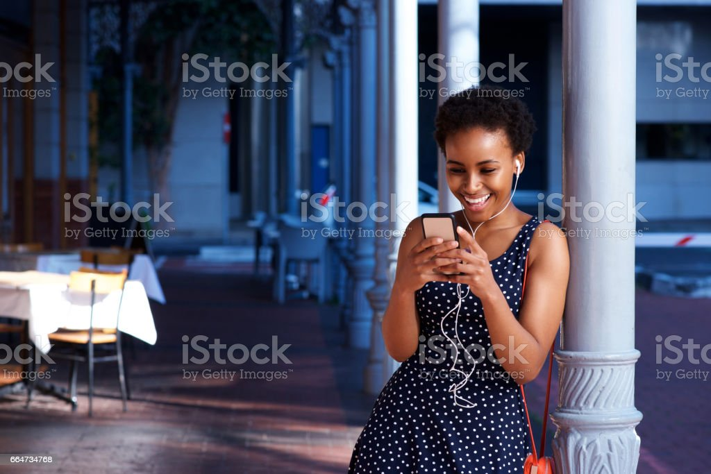 smiling young black woman with earphones looking at cellphone stock photo