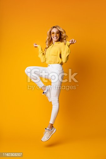 Excited Blonde Woman Having Fun, Jumping On Yellow Studio Background