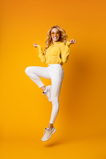 istock Smiling Young Blonde Woman Jumping In Air 1162303207