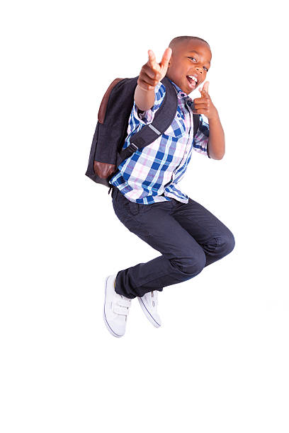 A smiling young boy jumping and putting his thumbs up stock photo