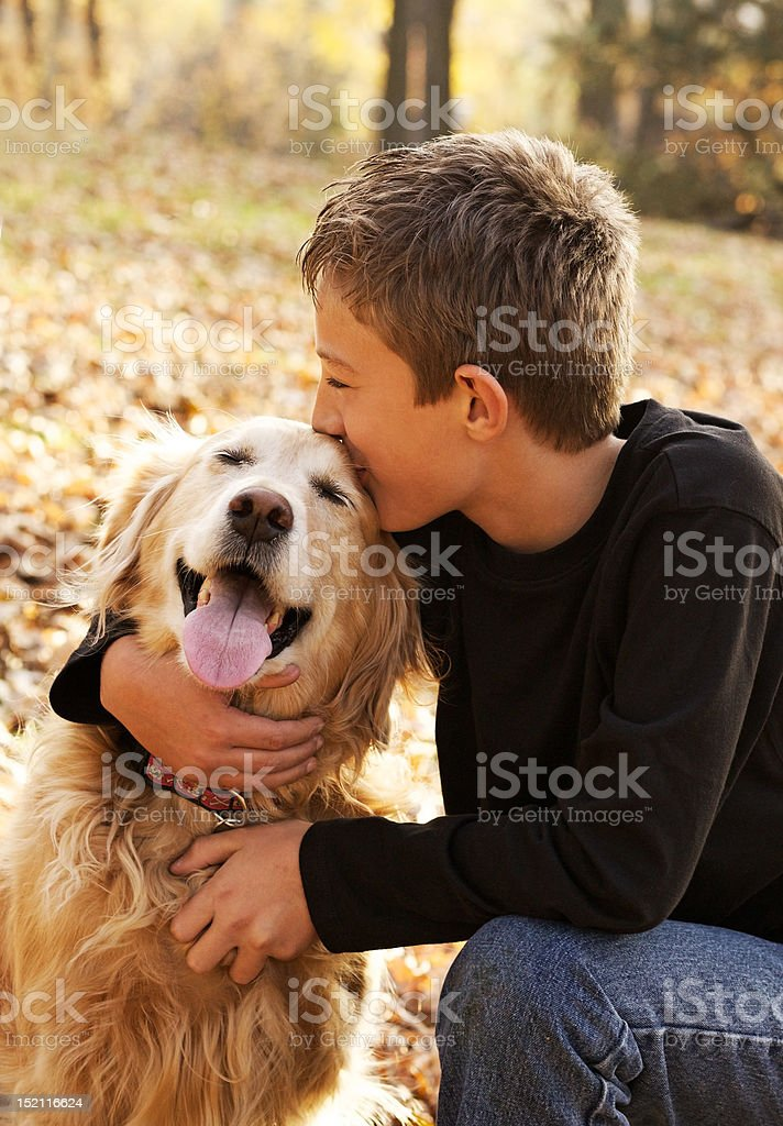 Smiling young boy kissing his dog stock photo
