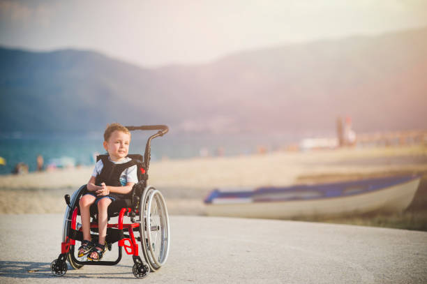 Smiling young boy on the wheelchair by the sea Smiling young boy on the wheelchair by the sea als stock pictures, royalty-free photos & images