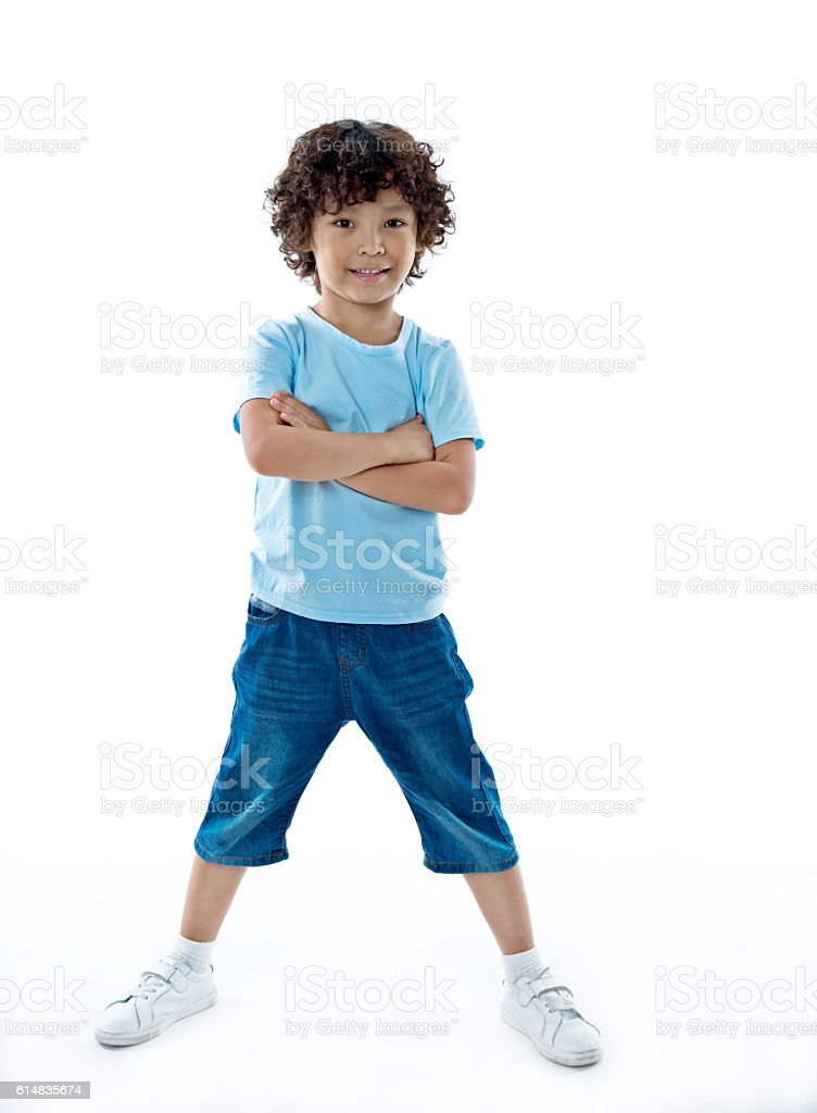 Smiling young boy standing against white background stock photo