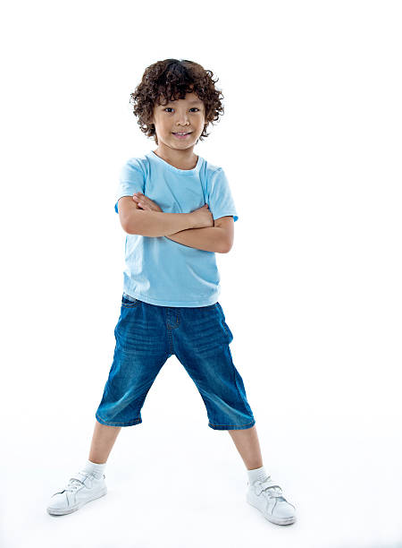Smiling young boy standing against white background – Foto