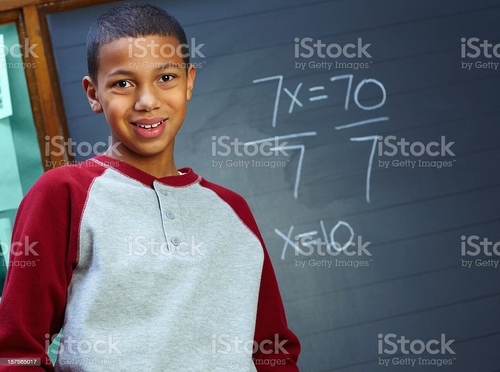 Smiling young boy standing in front of the blackboard royalty-free stock photo