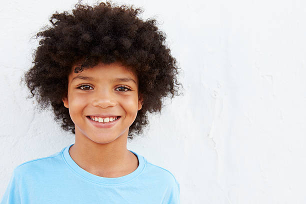 Smiling Young Boy Standing Outdoors Against White Wall Smiling Young Boy Standing Outdoors Against White Wall 8 9 years stock pictures, royalty-free photos & images