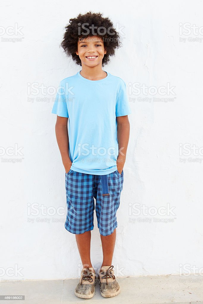 Smiling Young Boy Standing Outdoors Against White Wall stock photo