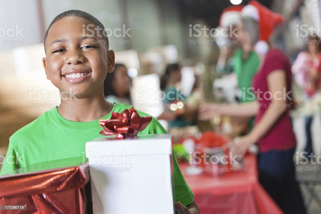 Smiling young boy with Christmas gift at a charity toy drive stock photo