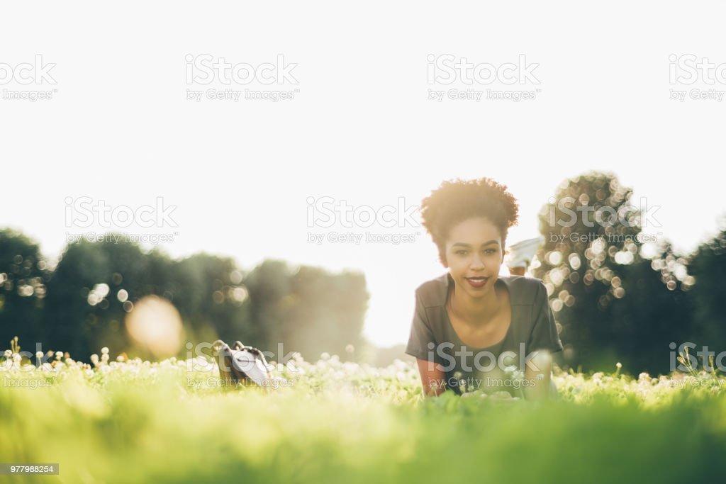Lächelnde junge brasilianische Studentin auf dem Rasen – Foto