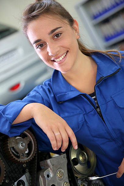 Smiling young brunette student in auto mechanics stock photo