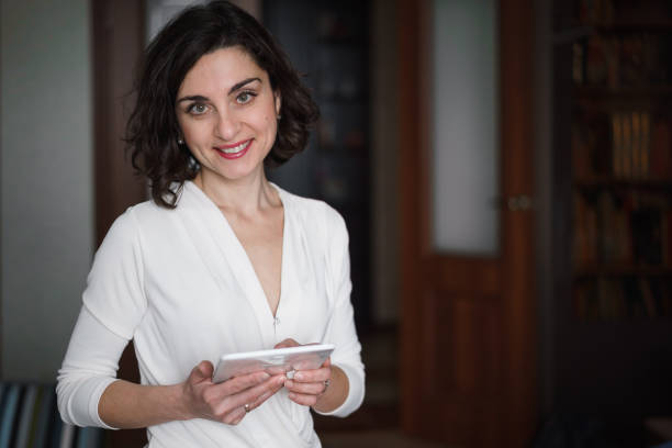 smiling young brunette woman in light clothes is in home interior. she's holding an electronic tablet. - judaizm zdjęcia i obrazy z banku zdjęć