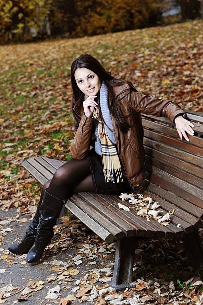 lächelnde junge brunette frau sitzt auf der bank im herbst zeit - damen rock braun stock-fotos und bilder