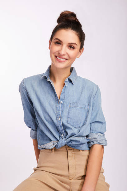 Smiling young brunette woman wearing casual clothing on gray stock photo