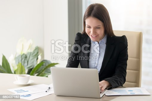 istock Smiling young business lady working with laptop, looking at screen 680437182