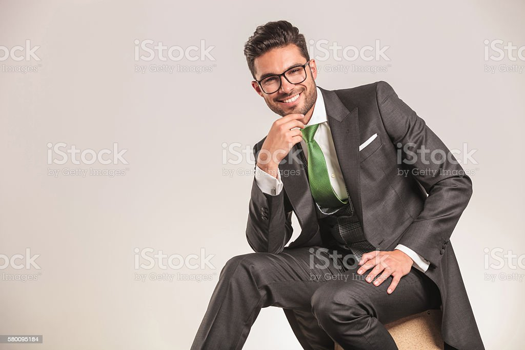 Smiling young business man holding his hand to the chin stock photo