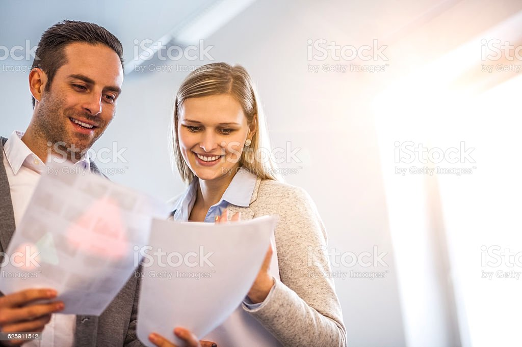 Smiling young business people reviewing documents in office – Foto