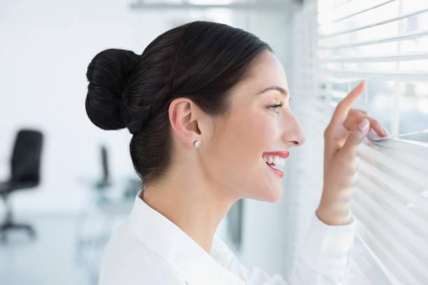 jeune entreprise souriant furtivement à travers des stores au bureau - cosmetique store photos et images de collection
