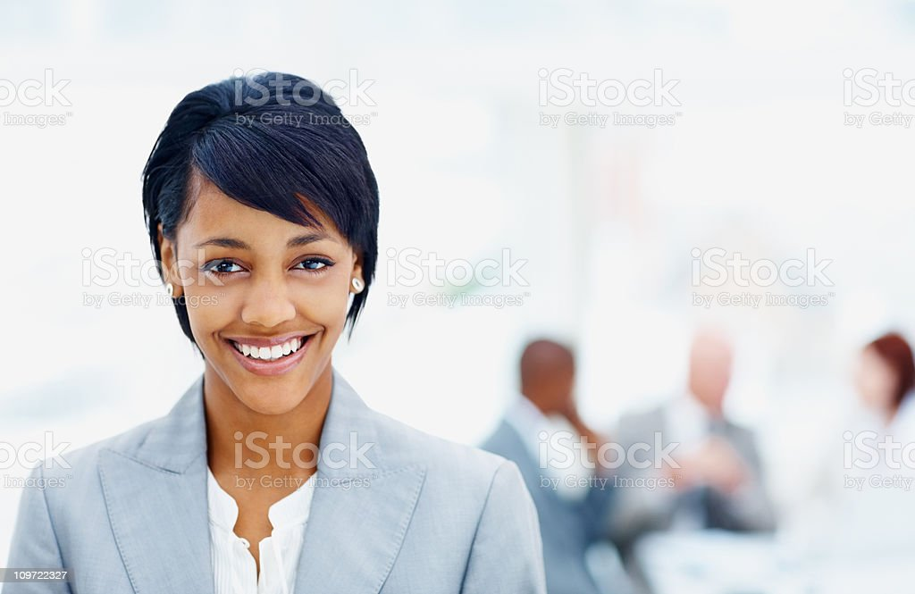 Smiling young business woman with her team in background royalty-free stock photo