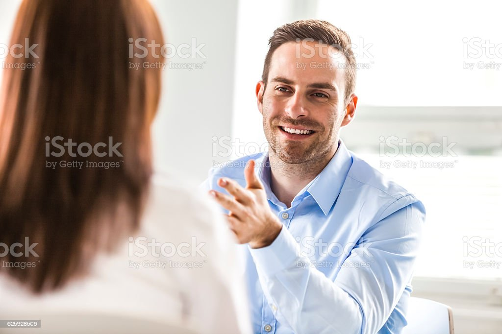 Smiling young businessman discussing with female colleague in office – Foto