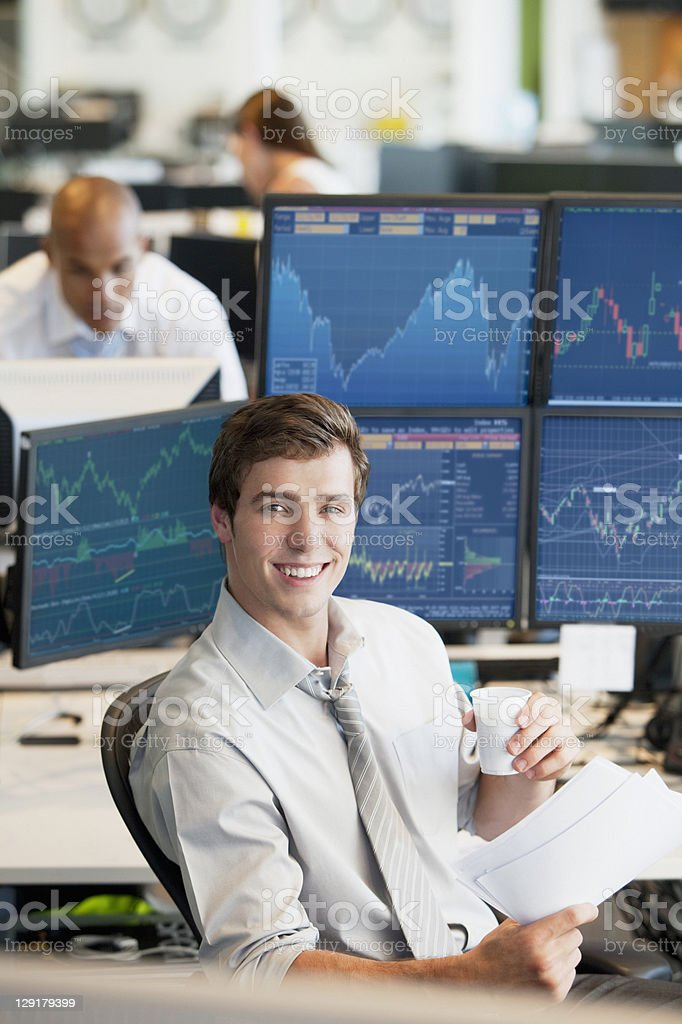Smiling young businessman having coffee stock photo