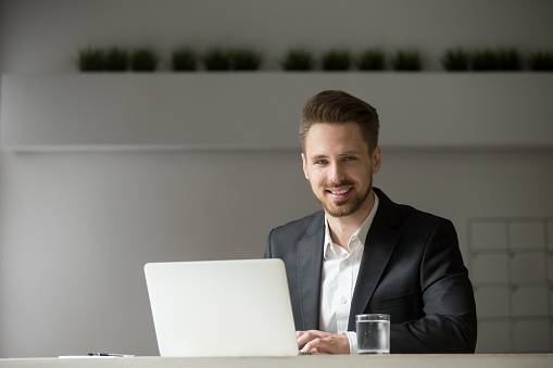 825082848 istock photo Smiling young businessman in suit with laptop looking at camera 912234880