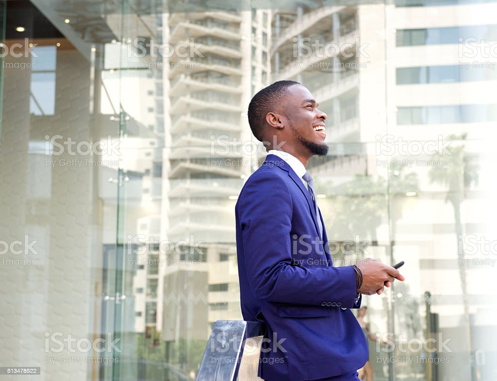 Smiling young businessman in the city stock photo